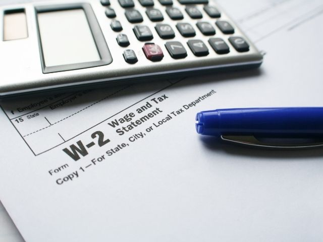 How to calculate AGI from W2 form with calculator next to blue pen