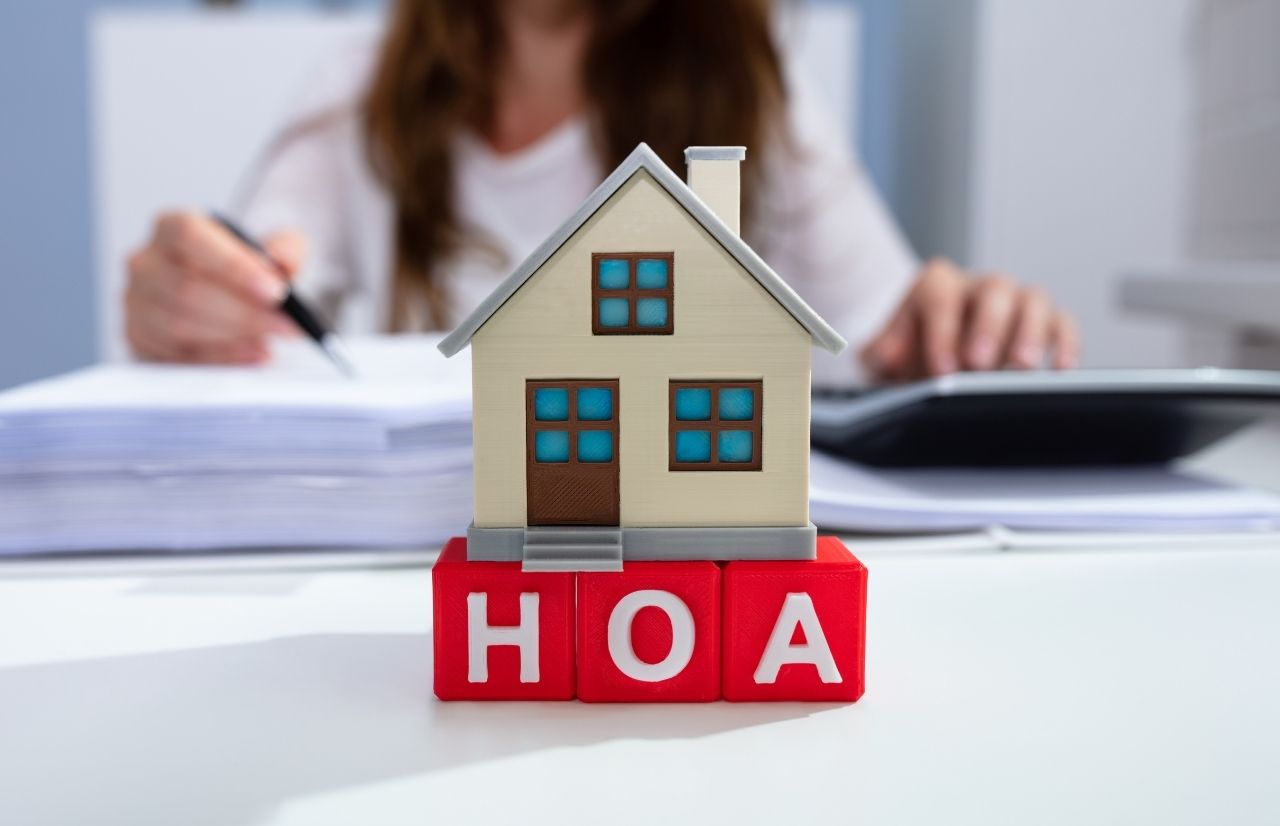 Are HOA Fees tax deductible with toy house on top of red letters HOA